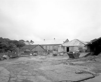 View from SE of buildings at SW corner of the mill complex, with curved concrete roof of calender house beyound.