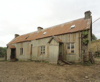 General View of former farm house from South showing tin sheeted roof and wall