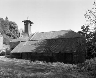 Auchenblae, Burnett Street, Den Mill View from north of north side of mill, with kiln occupying the east (left) end of the mill range, and the water wheel (obscured by vegetation) situated on the west gable (far right)