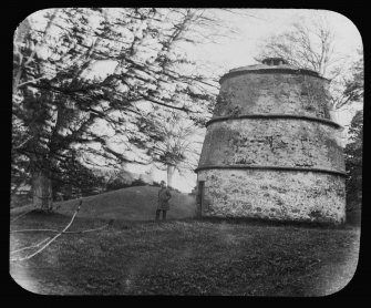 General view of the dovecot at Luffness House, with a male figure standing beside it.
