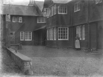 View of Skirling House courtyard with wrought iron work details and a woman standing outside