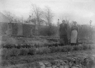 View of Skirling House garden with wrought iron work details and two women