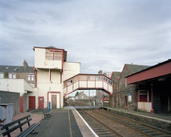 View from west of wooden tower and overbridge (left), rubble-built station offices (right), and part of platform canopy (far right)