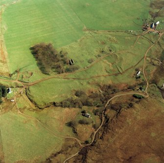 Oblique aerial view centred on the remains of the church with farmhouse, barn and farmsteading adjacent, taken from the WNW.
