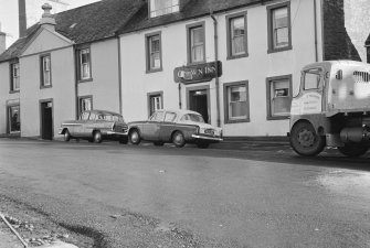 View of the Crown Inn, 36 Main Street, Glenluce from south west, showing James Muir's premises and cars and lorry.