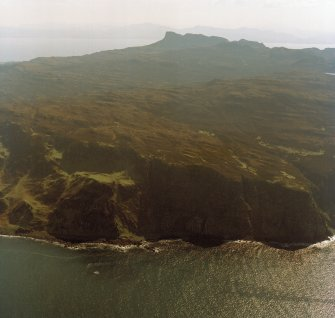 General oblique aerial view of the west side of Eigg with the fort in the foreground and the Sgurr fort beyond, taken from the NNW.