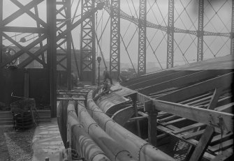 Photograph recording the construction of Granton Gasworks, Edinburgh showing the separate lifts of the gasholder and work being done on the sheeting of the crown.