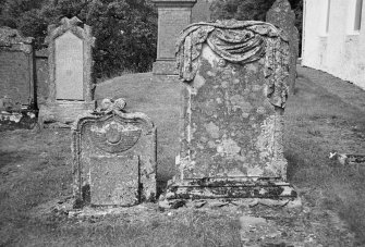 Glendevon Parish Church, Churchyard. General view of two tombstones. The first with a winged soul, the second with a carved stone 'drape' over the top.