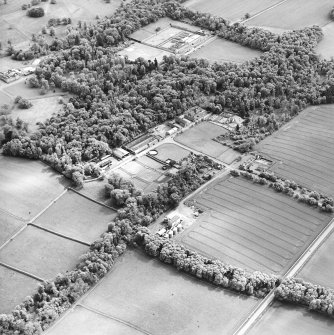 Oblique aerial view centred on the farmsteading, kennels and cottage with country house and formal garden adjacent, taken from the N