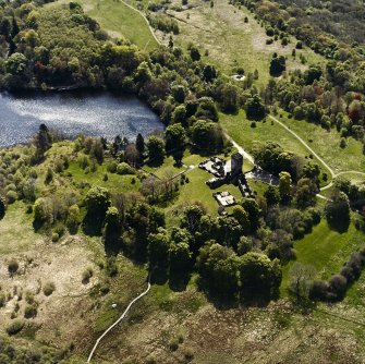 Oblique aerial view centred on the remains of the castle and tower, taken from the NW.