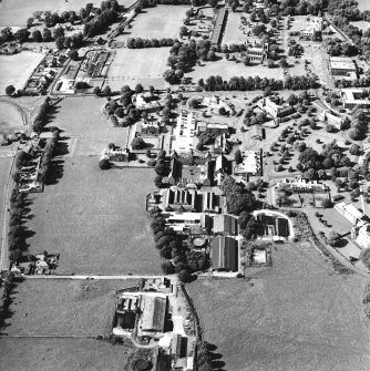 Oblique aerial view centred on the hospital and the church, taken from the SE.