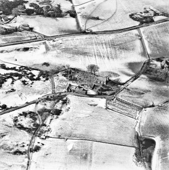 Oblique aerial view centred on the churches, burial-ground and buildings, taken from the E.