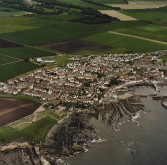 Oblique aerial view of St Monance centred on the village, church and harbour, taken from the SSW.