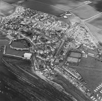 Oblique aerial view of St Monance centred on the village and harbour, taken from the ESE.