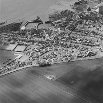 Oblique aerial view of St Monance centred on the village, harbour, church and burial ground, taken from the NNE.