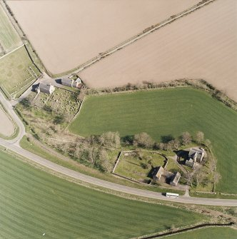 Oblique aerial view centred on the farmsteading, manse and walled garden, with the church, churchyard and war memorial adjacent, taken from the NW.
