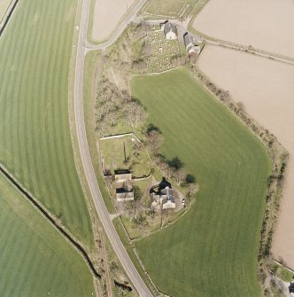 Oblique aerial view centred on the farmsteading, manse and walled garden, with the church, churchyard and war memorial adjacent, taken from the WSW.