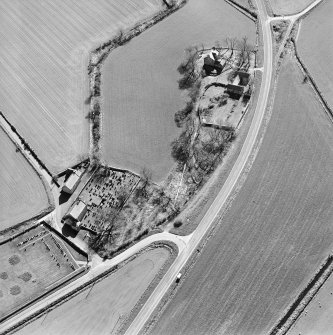 Oblique aerial view centred on the farmsteading, manse and walled garden, with the church, churchyard and war memorial adjacent, taken from the NNE.