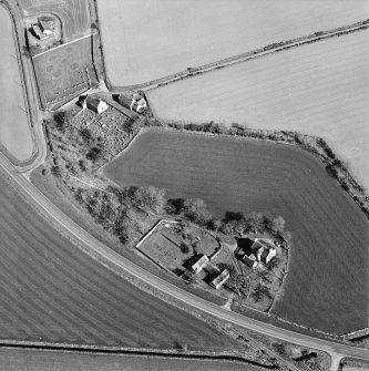 Oblique aerial view centred on the farmsteading, manse and walled garden, with the church, churchyard and war memorial adjacent, taken from the WNW.