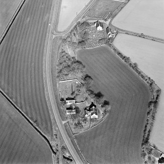 Oblique aerial view centred on the farmsteading, manse and walled garden, with the church, churchyard and war memorial adjacent, taken from the SW.