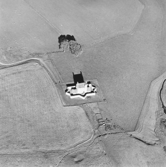 Oblique aerial view of Corgarff castle centred on the tower-house with the remains of a pond, quarry, farmstead and the cropmarks of a building adjacent, taken from the SW.