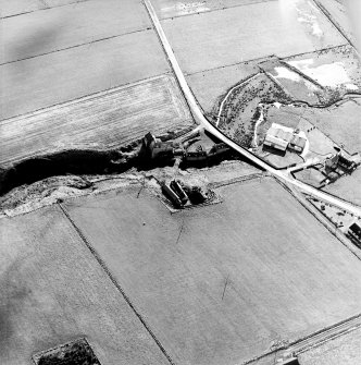 Oblique aerial view of the watermills, bridges, stables and cottage, taken from the NW.
