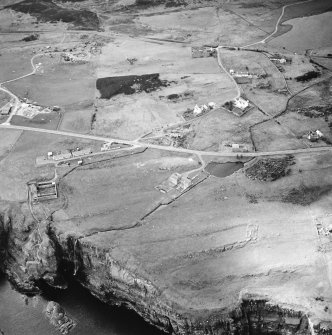 Oblique aerial view centred on the watermill with the house, curing yard, farmsteads and council houses adjacent, taken from the ESE.