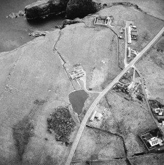 Oblique aerial view centred on the watermill with the house, curing yard, farmsteads and council houses adjacent, taken from the NNE.