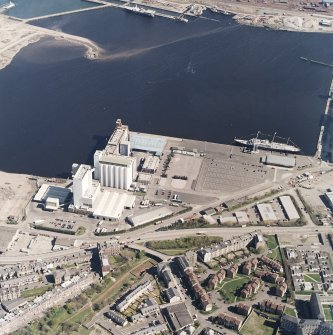 Oblique aerial view centred on the flour mills with the docks adjacent, taken from the SSW.