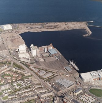 Oblique aerial view centred on the flour mills with the breakwater and docks adjacent, taken from the SSE.
