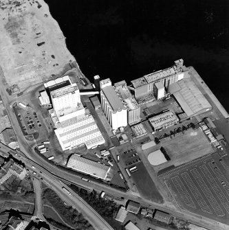 Oblique aerial view centred on the flour mills with the docks adjacent, taken from the SE.
