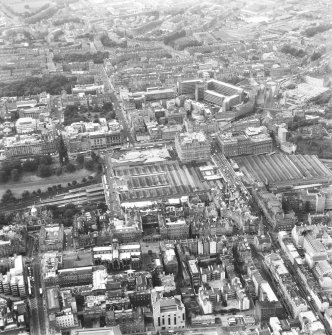 Oblique aerial view of centre of Edinburgh including Princes Street and the New Town at top of photograph, Waverley Station to right, Cowgate, Solicitors' Library at bottom and Bank of Scotland on The Mound to left.