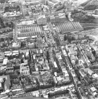 Oblique aerial view of centre of Edinburgh including St James' Centre at top of photograph, Jeffrey Street at right, Old College at bottom and St Giles' Cathedral at left.