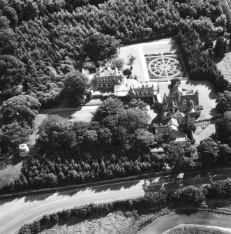 Oblique aerial view of house, gardens, stables and doocot from N.