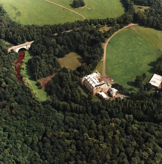 Oblique aerial view centred on the country house and garden with bridge adjacent, taken from the WSW.