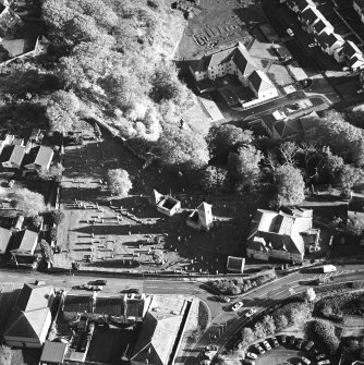 Oblique aerial view of Penicuik, ST Kentigern's Church and Churchyard centred on a church, churchyard and burial ground, with a mausoleum, other church and hearse house adjacent, taken from the NW.