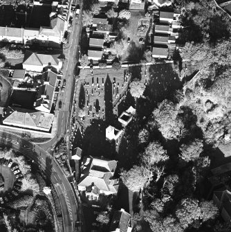 Oblique aerial view of Penicuik, ST Kentigern's Church and Churchyard centred on a church, churchyard and  burial ground, with a mausoleum, other church and hearse house adjacent, taken from the SW.