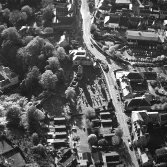 Oblique aerial view of Penicuik, ST Kentigern's Church and Churchyard centred on a church, churchyard and burial ground, with a mausoleum and other church and hearse house adjacent, taken from the NE.
