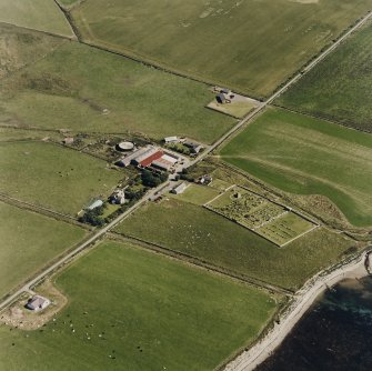 Oblique aerial view of Orphir, St Nicholas's Church, burial-ground and the Earl's Bu with mill, taken from the SW. Also visible is the Bu of Orphir farmhouse and farmsteading.