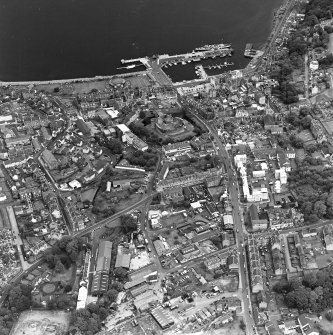 Oblique aerial view of Rothesay, taken from the SW, centred on the town.  A harbour is visible in the top half of the photograph.  A castle and the Winter Gardens are visible in the top centre of the photograph.