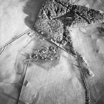 Oblique aerial view centred on the remains of the four gun-emplacements and command and control building with the remains of the accommodation camp in the small plantation, taken from the WSW.