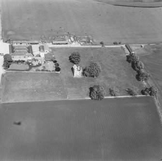 Oblique aerial view from W with farm buildings to N.