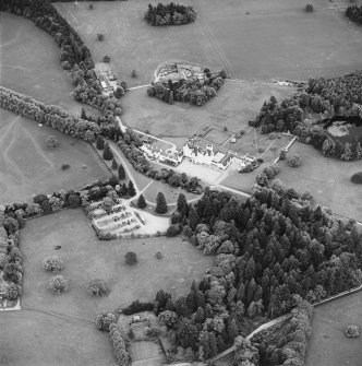Oblique aerial view of Blair Castle centred on the country house and garden, with the remains of a church adjacent, taken from the NNE.