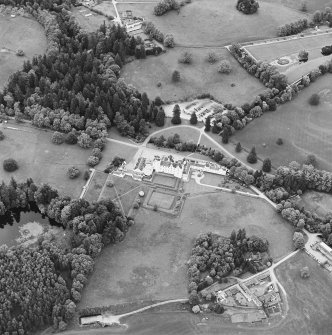 Oblique aerial view of Blair Castle centred on the country house and garden, with the remains of a church adjacent, taken from the SSW.