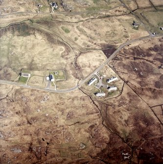 Oblique aerial view centred on the church, burial ground and manse with the houses adjacent, taken from the SW.