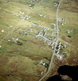 Oblique aerial view centred on remains of the horizontal mills with the remains of the broch adjacent, taken from the WSW.