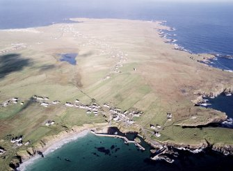 General oblique aerial view looking across the harbour, crofting township and lazy beds towards the townships and lighthouse, taken from the SE.
