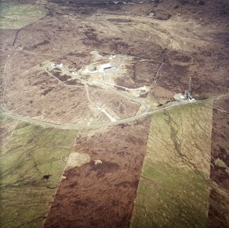 Oblique aerial view centred on the radar station with the remains of the chambered cairn and aisled house adjacent, taken from the SSE.