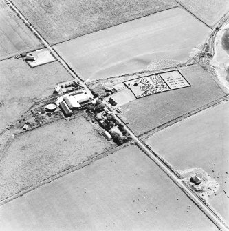 Oblique aerial view of Orphir, St Nicholas's Church, burial-ground and the Earl's Bu with mill, taken from the W. Also visible is the Bu of Orphir farmhouse and farmsteading.