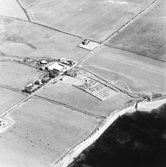 Oblique aerial view of Orphir, St Nicholas's Church, burial-ground and the Earl's Bu with mill, taken from the WSW. Also visible is the Bu of Orphir farmhouse and farmsteading.